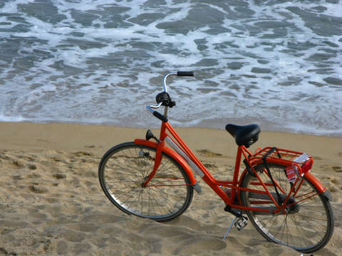 Orange bicycle on a beach in barcelona