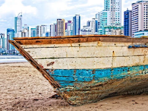 Abandoned boat on city beach
