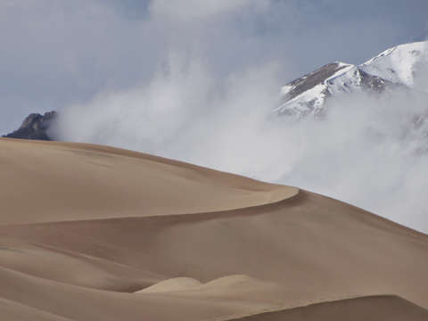 Sand dunes snow capped mountains