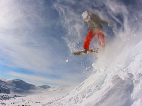 Snowboarder launching at copper mountain