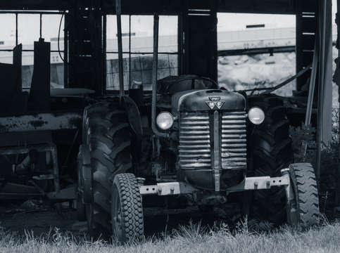 Old tractor in the barn black and white