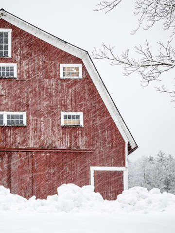 Old red barn winter storm