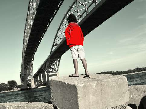 Boy in red under bridge