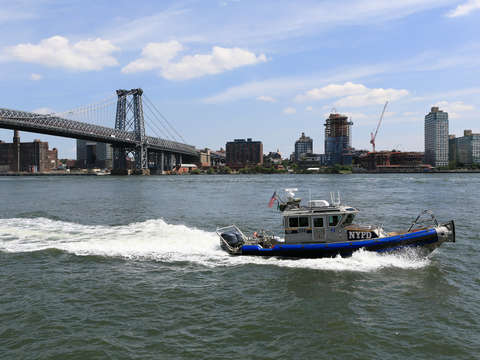 Police boat in front of williamsburg bridge