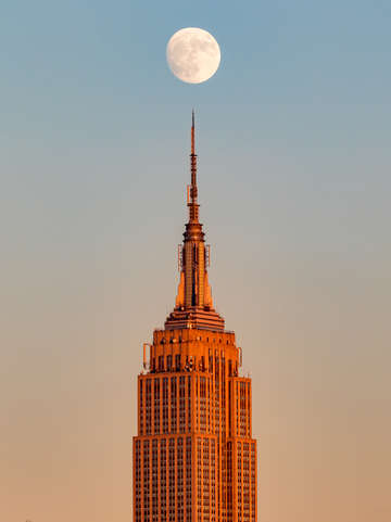 Moon rising above empire state building