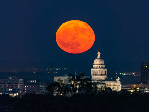 Full moon rise over the texas capitol