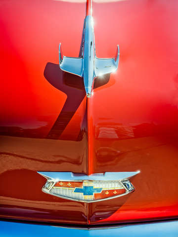 Hood ornament on a red 55 chevy