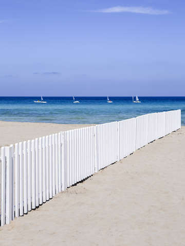 Fence on beach with boats