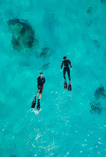 Aerial photo of snorkelers in a sapphire blue sea