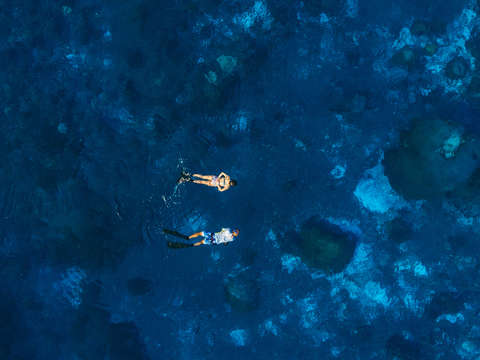 Aerial photo of snorkelers in a cobalt blue sea
