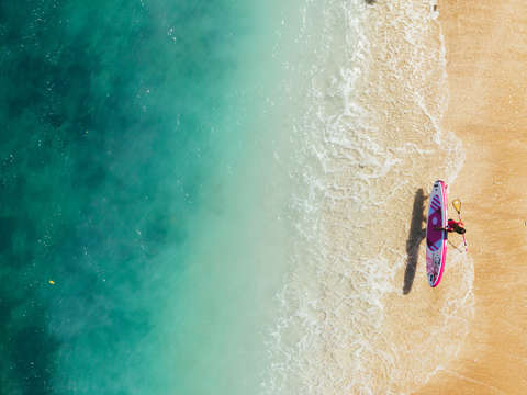 Aerial view of a surfer beside a sapphire blue sea