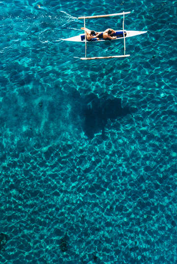 Aerial view of a sea kayak paddling across the blu