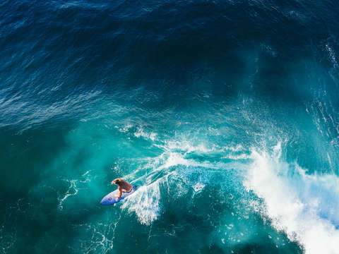 Aerial view of a surfer riding a sapphire blue wav