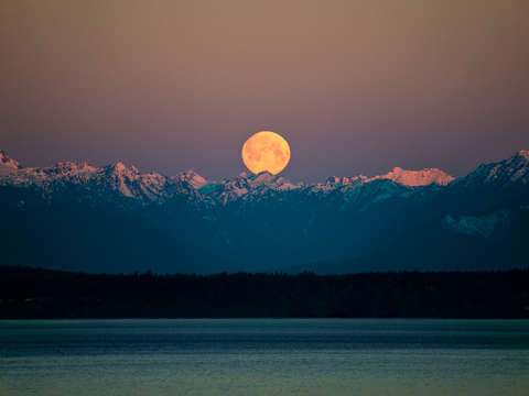 Full moon in seattle setting over olympic mountain