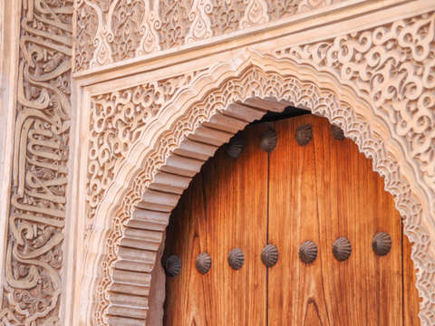 Wooden door with decorative stone carving alhambra